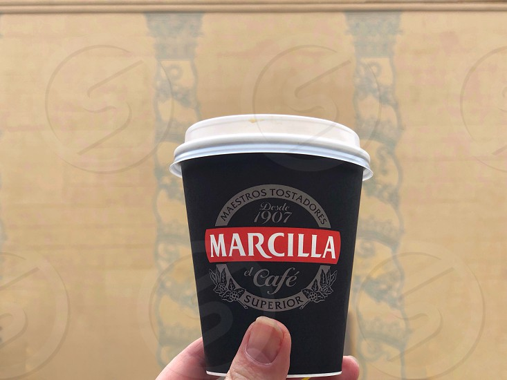 Walk around Barcelona.  Disposable paper coffee cup against the background of a yellow wall. photo