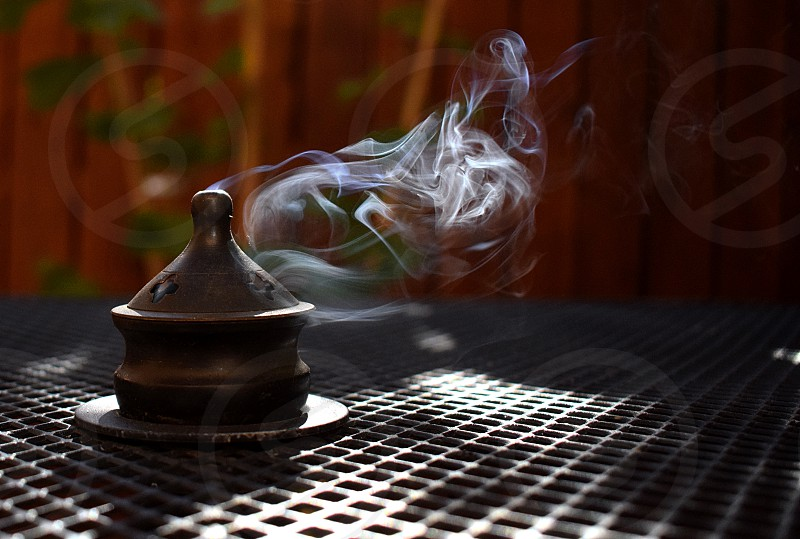 Smoke drifting through sunbeams from a metal incense burner. photo