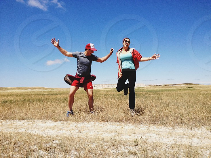 two people jumping on green and brown field photo