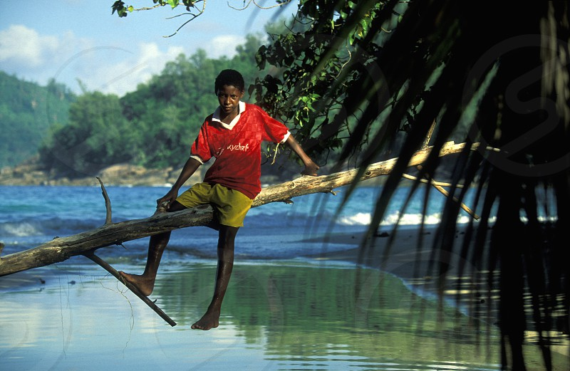 a boy on river and a Beach on the coast if the Island Mahe of the seychelles islands in the indian ocean photo