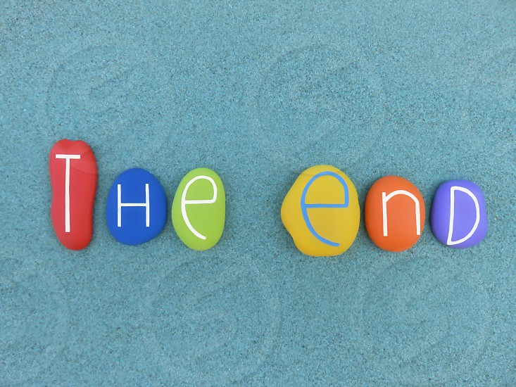 The end text composed with multi colored stones over green sand                               photo