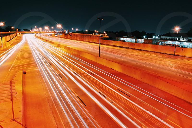 white light trails on orange brick road at night photo