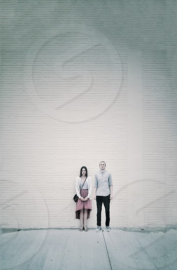 woman in white cardigan and red skirt  standing besides a man in grey dress shirt and black pants in front of white concrete wall photo