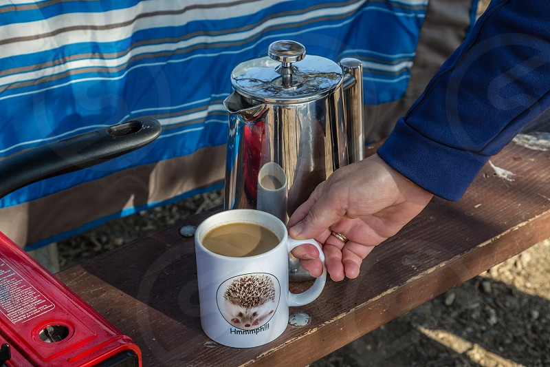 Grabbing a cup of coffee while camping photo