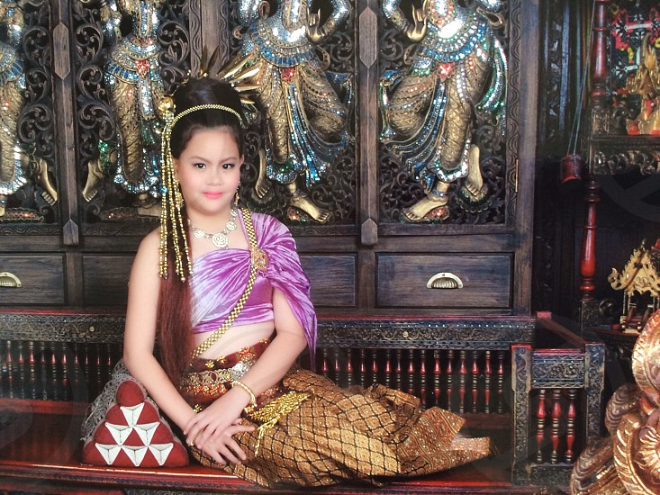 Close up portrait of Asian woman with purple Thai dress sit on wooden seat photo