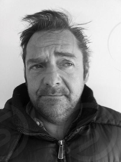 man wearing a black collared zip up jacket photo