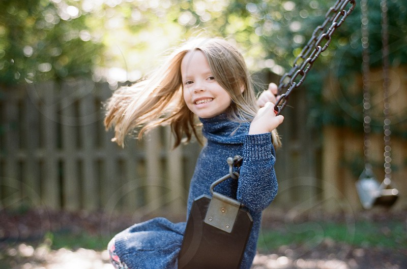 girl swing park family fun playground daughter movement outside sun light fall photo