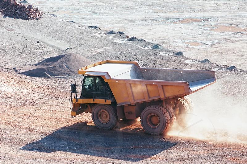 dumper truck driving around in a open pit mine. quarry. photo
