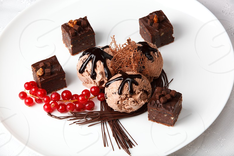 Scoops of creamy chocolate ice cream served with chocolate bonbons and a bunch of fresh red currants garnished with chocolate strands for a gourmet dessert photo