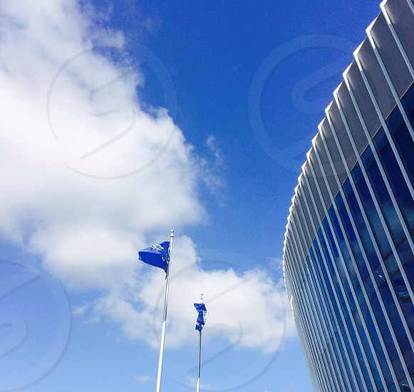 blue flags on flag poles outside round building photo