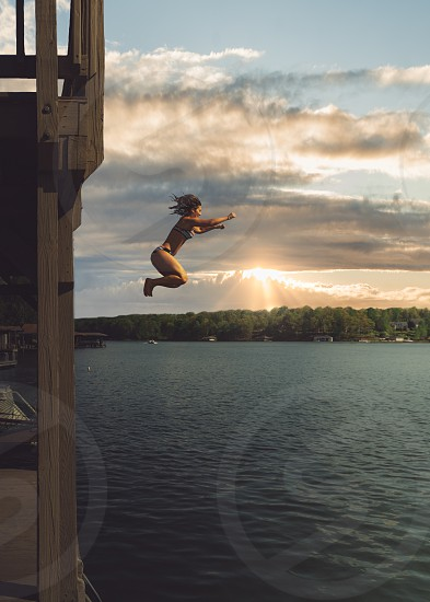 Lake dock jumping in the water sky sunset photo