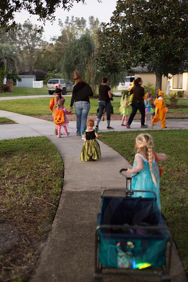 Kids trick or treating around the neighborhood with a wagon on Halloween. photo