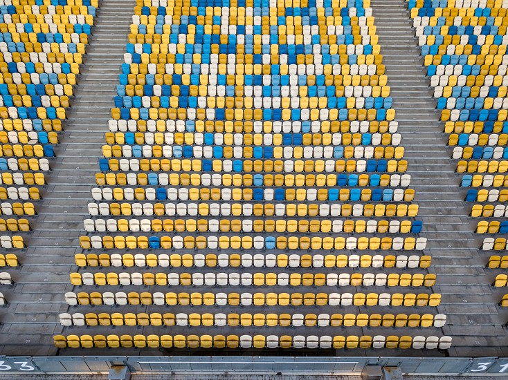KIEV UKRAINE - July 19 2018. National Sports Complex Olimpiysky aerial view from drone on empty even rows tribunes of stadium with yellow and blue seats before soccer match in the summer time. photo