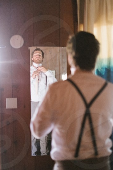 man in white dress shirt fixing self in front the mirror photo