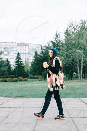 woman with  black long hair in black long sleeved shirt black pants and black and orange shoes walking on sidewalk while holding paper cup photo