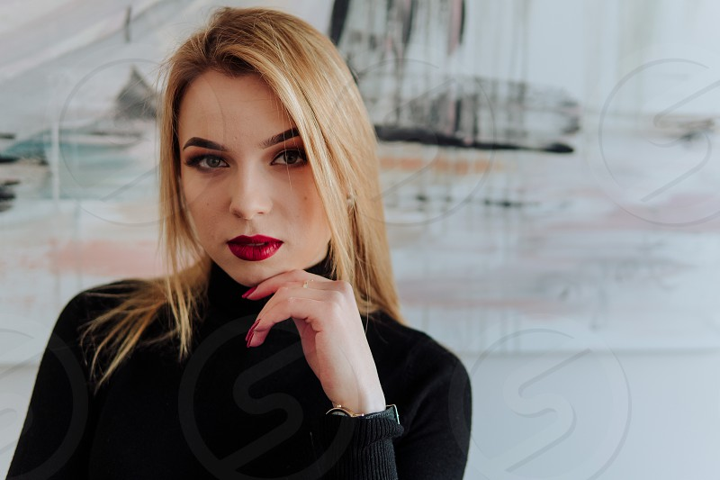 Young beautiful business woman wearing black shirt looking seriously and supports her chin with the fingers photo