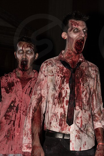 zombie man in white dress shirt and black necktie full of red blood stains next to zombie man in white red gingham button up shirt full of red blood stains photo
