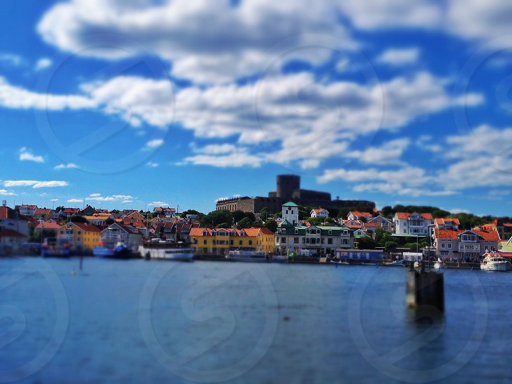 tilt shift photography of city by the sea under white clouds and blue sky photo