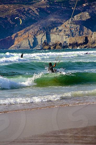 Hitting the waves hard. Kitesurfing in Guincho Portugal photo