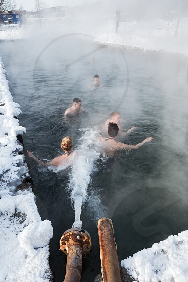 ANAVGAY VILLAGE KAMCHATKA PENINSULA RUSSIAN FAR EAST - FEB 02 2013: People relaxing in geothermal spa in hot spring pool with natural thermal mineral water having balneological properties in winter. photo