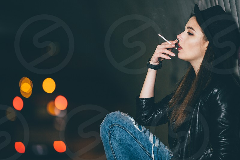 woman in black leather jacket smoking cigarette photo