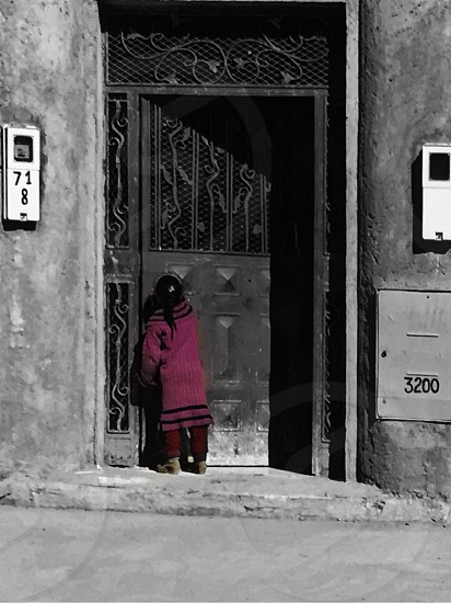 girl in pink coat knocking at metal door photo