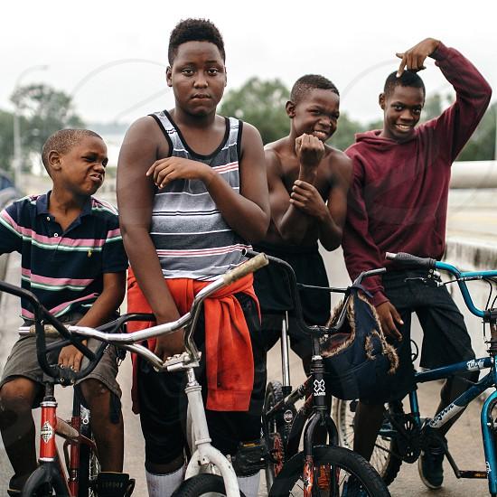 4 boys riding bicycles smiling photo