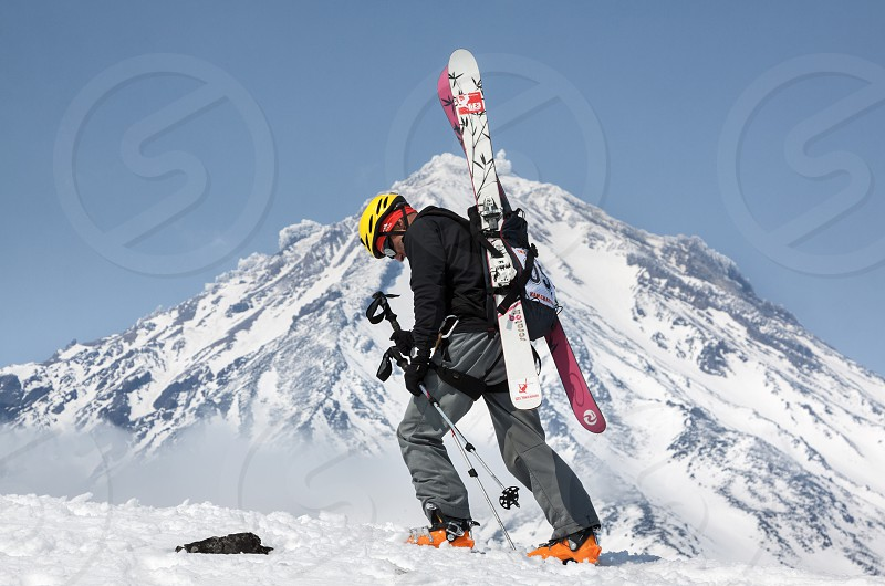 AVACHA VOLCANO KAMCHATKA RUSSIA - APR 21 2012: Open Cup of Russia on ski-mountaineering. Ski mountaineer climbing on mountain with skis strapped to backpack on background active Koryaksky Volcano. photo