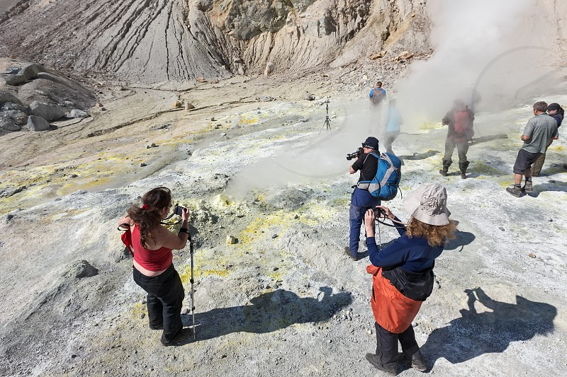 KAMCHATKA RUSSIA - SEPTEMBER 11 2013: Group photographers takes a picture volcanic landscape and active sulfur fumaroles ejecting steam and gas in crater of active Mutnovsky Volcano on Kamchatka. photo