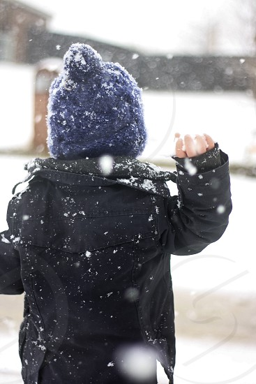 Throwing a snowball during a snow storm.  photo