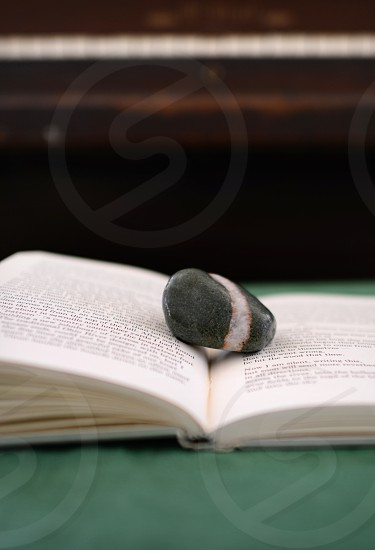 An open book with a single stone on it photo