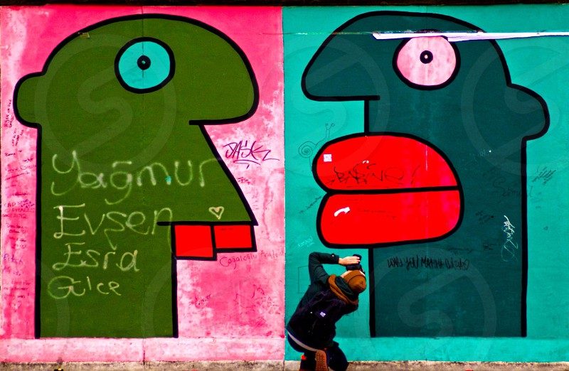 person in black jacket looking green and teal human graffiti photo