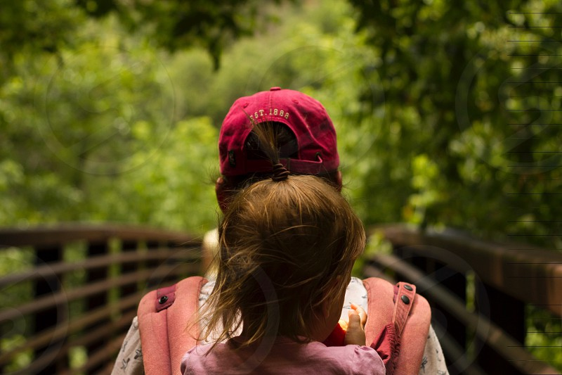 child wearing pink shirt riding on pink backpack carrier carrier by person wearing red snapback cap walking on brown wooden bridge surrounded by trees photo