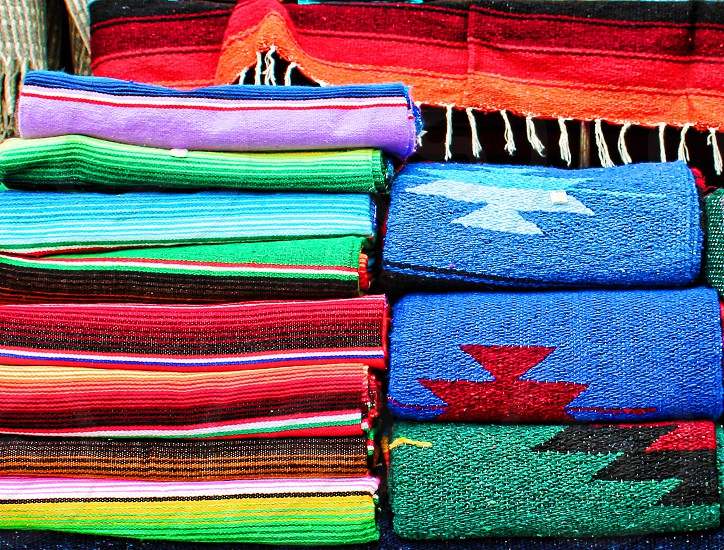 Brightly colored Mexican blankets and serapes are stacked one on top of each other. photo