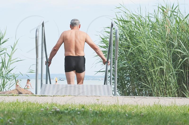 Old Man Entering Lake Balaton on Metal Stairs on a Summer Day photo