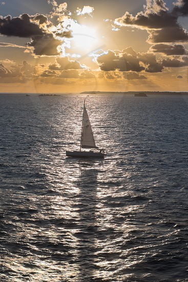 Small sailing boat / yacht on the ocean at sunset photo
