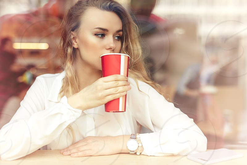 Woman Drink Her Hot Coffee While Sitting In Cafe. Portrait Of Stylish Smiling Woman In Winter Clothes Drinking Hot Coffee. Female Winter Style. - Image photo
