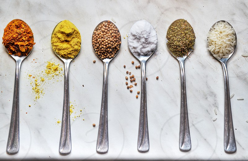 6 silver spoons with different spices photo