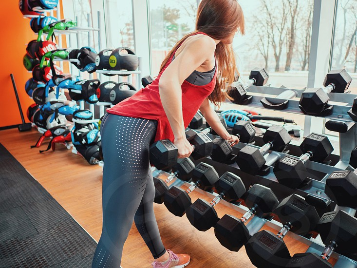 beautiful slender girl in sportswear takes a dumbbell in the gym. Health sport concept. photo