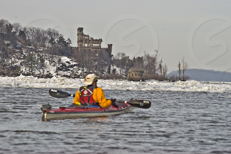 person yellow jacket in grey and red kayak in water under grey sky photo