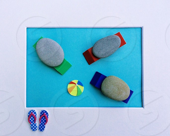 green red and blue sun loungers with stone on top artwork photo