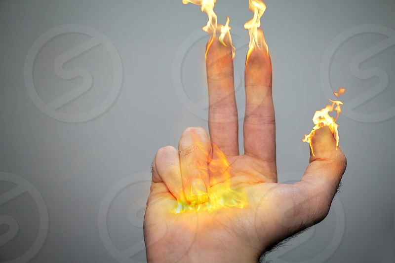 Right hand and fingers are on fire like candles or torches. Being an inspiration of the Hanukiah (menorah). 8 fingers symbolizing the menorah candles and a big flame in the middle of the palm symbolizes the Hshamash.Three lit candles. photo