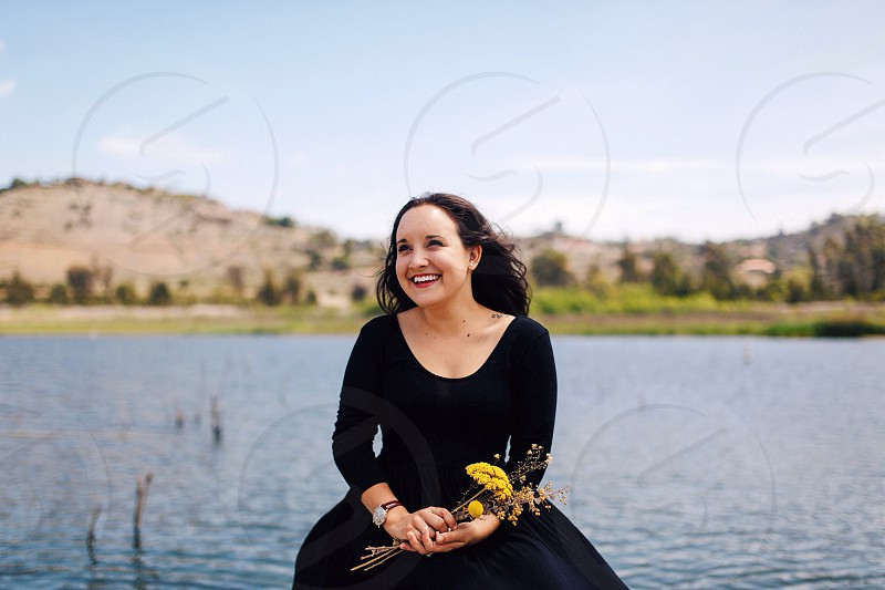 woman in black scoop neck long sleeved dress holding yellow flowers and smiling photo