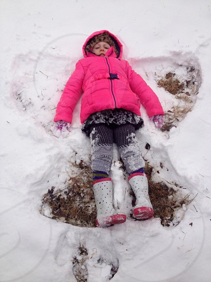 Girl child in pink jacket making snow angel photo