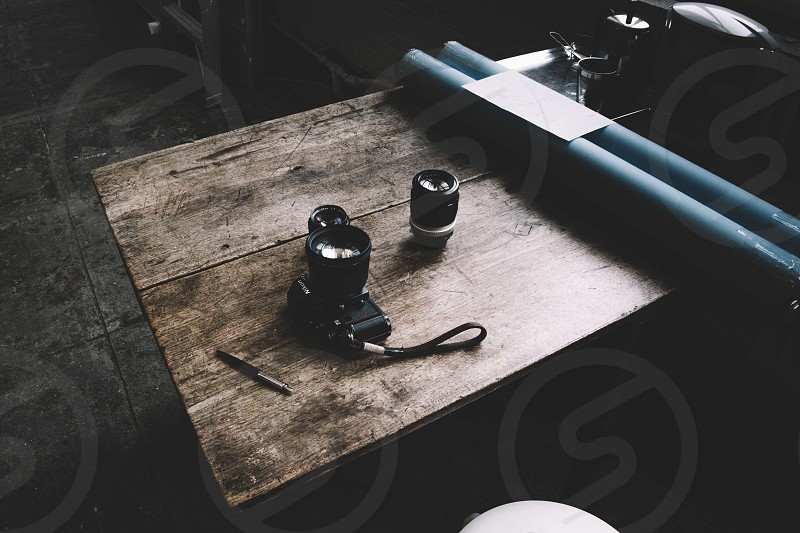 dslr camera on wooden table beside black camera lens near 2 green pipe photo