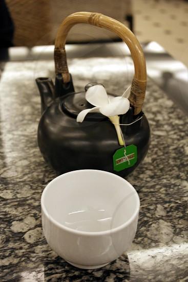 black ceramic tea pot with brown handled beside the white ceramic bowl photo