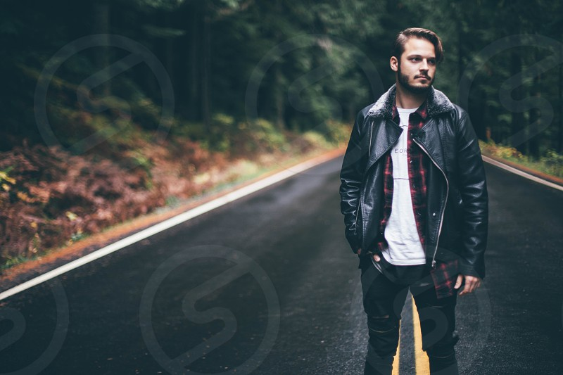 man in black leather zip jacket with plaid shirt underneath and black skinny jeans standing on the middle of the concrete road in the middle of the tall trees at day time photo