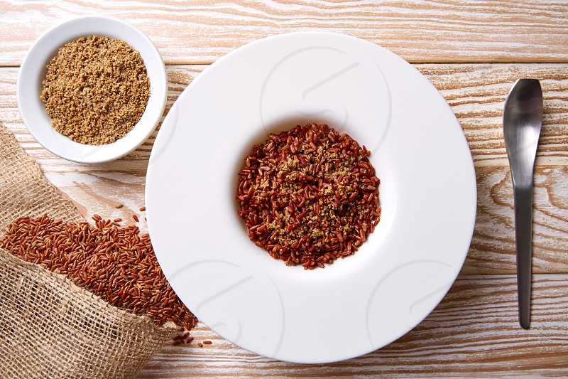 Red wild rice with sesame gomasio seasoning in a white plate over wooden board photo