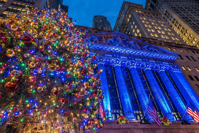 blue red gold and green bauble tree beside u.s. flag during nighttime photo