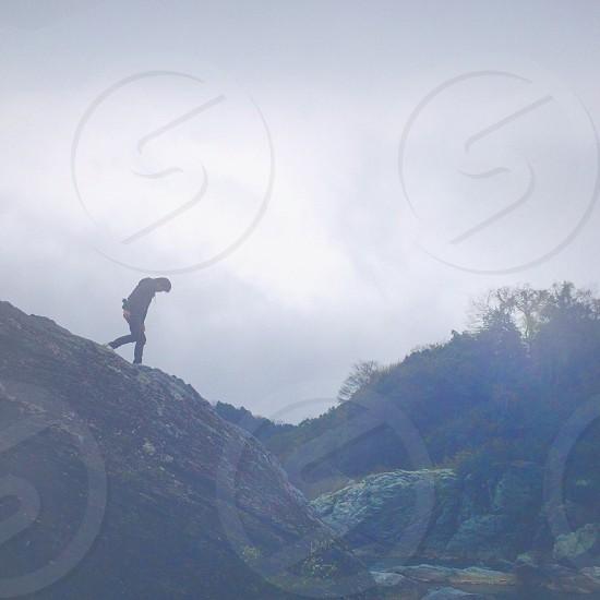 standing figure wearing black walking down rocky hill photo